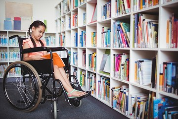 Girl in a wheelchair reading a book