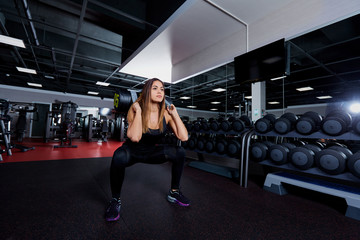 Beautiful sporty woman doing squat workout in gym.
