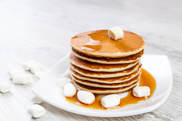 Tasty pancake on a white plate, wooden background, maple syrup