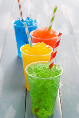 Colorful summer slushies on blue background