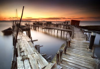 Ancient fishing pier with warm and beautiful sunset