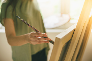 Cropped shot of artist makes paint brush strokes on canvas