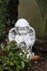 Kleiner Engel betet auf einem Grab
