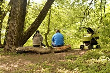 Молодая семья с ребенком, беседует  на природе