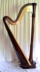 Concert grand pedal harp against white curtains