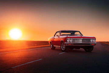 Retro red car standing on asphalt road at sunset Wall mural