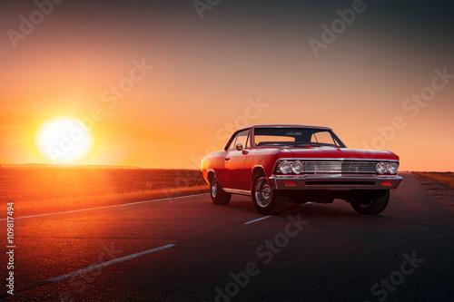 Fototapete Retro red car standing on asphalt road at sunset