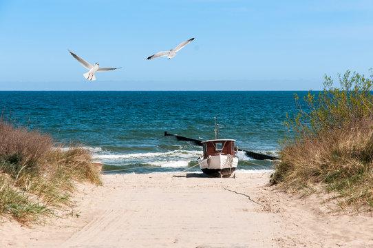 Strandaufgang mit Fischerbot und Möwen
