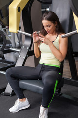 Woman using mobile phone on a break in health club