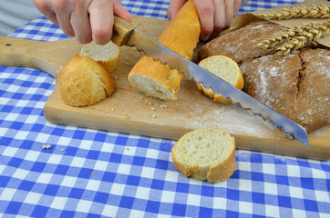 Someone cuts white baguette and dark bread with knife