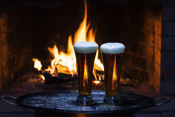 two beers with fireplace on background