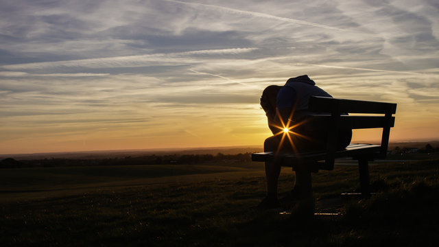 Sad unhappy silhouette man sitting with his head in his hands on a bench at sunset