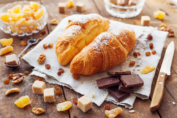 Breakfast background - pair of croissants with chocolate, sugar, ginger and walnuts on rustic wooden background.