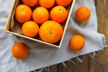 Box full of fresh oranges. Fruit harvest on rustic wooden table.