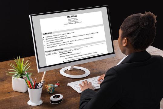Businesswoman Analyzing Resume On Computer