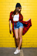 Beautiful young sexy girl posing and smiling near yellow wall background in sunglasses, red plaid shirt, shorts.