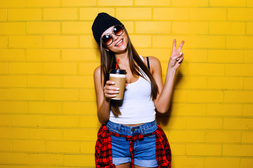 Beautiful young sexy girl drink coffee, smiling and posing near yellow wall background in sunglasses, red plaid shirt.