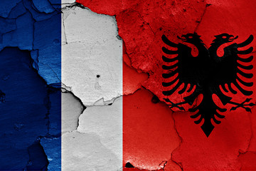 flags of France and Albania painted on cracked wall