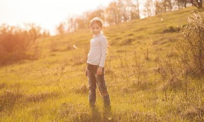 smiling little girl on sunlight in countryside