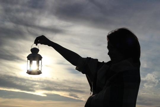 Girl silhouette with a candle lantern on backdrop of clouds and setting sun