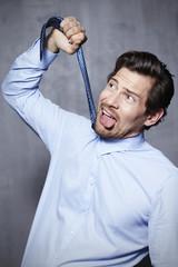 Businessman pulling tie in studio