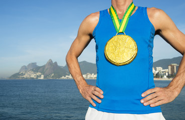 First place athlete wearing a large gold medal standing outdoors at Ipanema Beach, Rio de Janeiro, Brazil