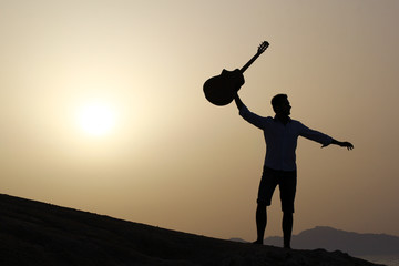 joyful guitarist with guitar up in the air