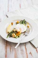 Green Griddled Asparagus with Poached Egg, Lemon and Sourdough Crumbs on a Plate, Light Background