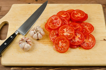 Red tomato slices, garlic and knife on chopping board