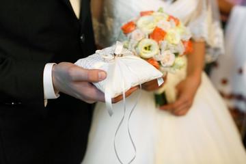 Groom holds in his arm wedding rings