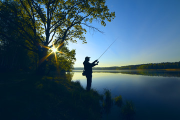 silhouette of a fisherman with a fishing rod on the shore of the lake, the river in the morning....