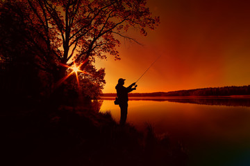 silhouette of a fisherman with a fishing rod on the shore of the lake, the river in the evening....