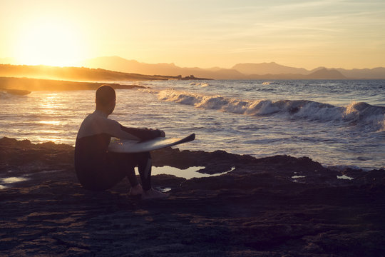 Young man surfer holding the surfboard while contemplating the waves at sunset.