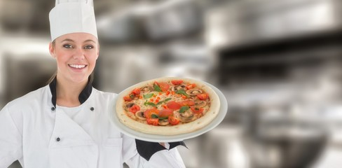 Composite image of portrait of a woman chef holding a pizza