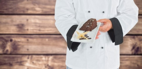 Composite image of close up on a chef holding a chocolate cake