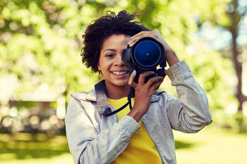 happy african woman with digital camera in park