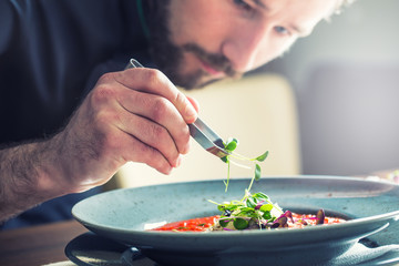 Chef in hotel or restaurant kitchen cooking, only hands. He is working on the micro herb decoration. Preparing tomato soup.