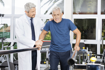 Doctor Motivating Senior Man To Walk In Fitness Studio