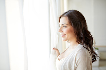 happy young woman looking through window at home