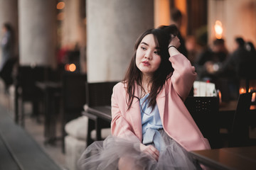 Beautiful Asian girl model in dress sitting at the old city background