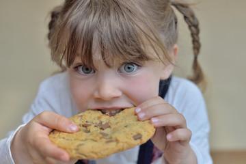 belle enfant mordant dans un cookie