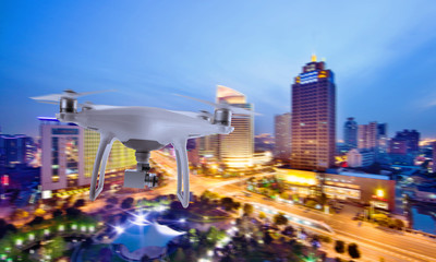 Drone quad copter with camera flying over the city center in night.
