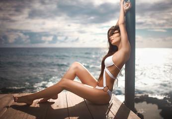 Gorgeous, lovely model posing on pier near ocean or sea.