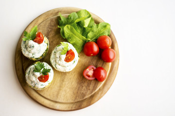 Spinach cupcakes with cheese cream frosting, green fresh onion on wooden board with cherry tomatoes and spinach leaves