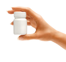 Woman's hand holding medical bottle with pills isolated on white background. Close up. High resolution product.