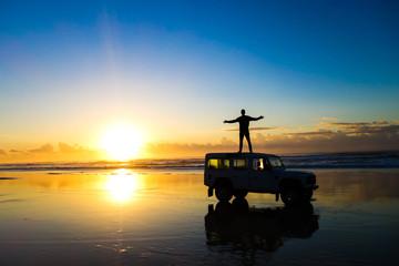 Sunrise on the beach with a land rover defender on Fraser Island Australia