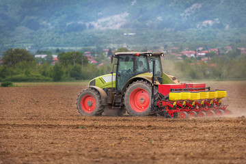 Fototapete - Farmer in tractor sowing crops at field with seed scattering agr