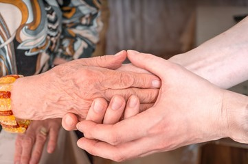 Man holds hands of eldery woman. Senior help concept.