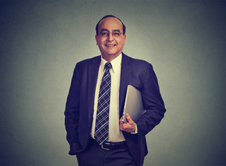 Businessman standing and holding a a laptop computer in his hand