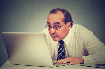 middle aged shocked business man sitting in front of laptop computer looking at screen